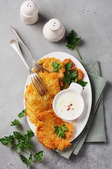 Frittelle di patate draniki, frittelle di patate vegetariane, servite con erbe fresche e salsa di yogurt all'aglio