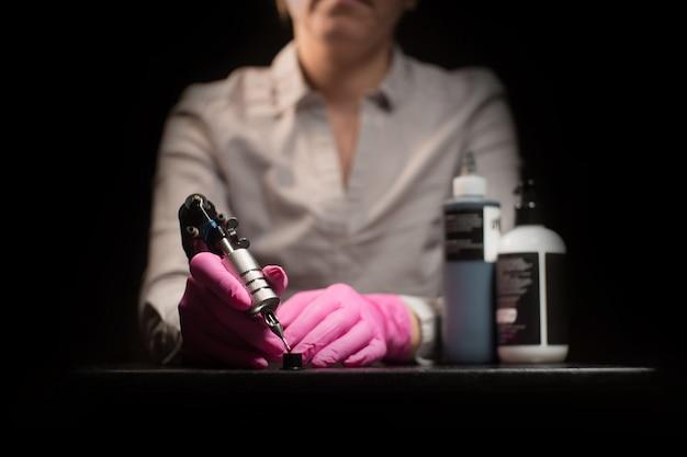 Disegna la vernice nera con la macchina per tatuaggio con i guanti