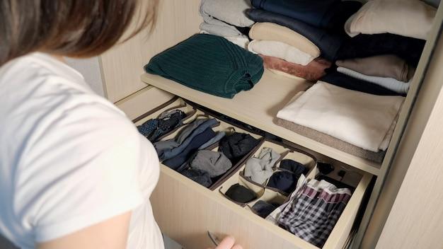 Il cassetto con la biancheria intima nell'armadio. ragazza che organizza i vestiti nell'armadio, primo piano.