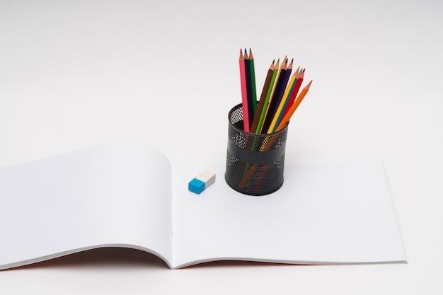 Album da disegno e matite colorate su sfondo bianco. di nuovo a scuola