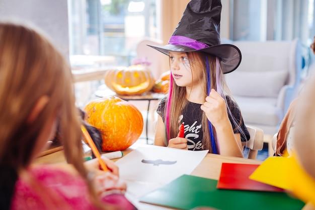 Pipistrello di disegno. bella ragazza dai capelli scuri con labbra viola che indossa il cappello da mago nero per halloween che disegna il piccolo pipistrello nero