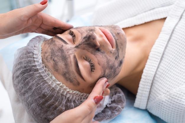 Disegnare una maschera nera sul viso del paziente. salone di bellezza.