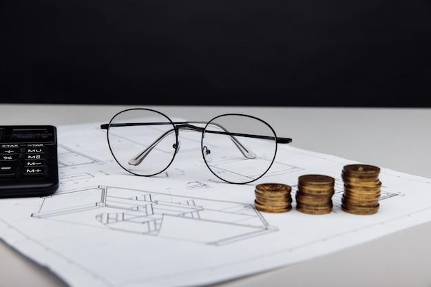 Bicchieri da disegno e calcolatrice con monete concetto di costo di costruzione immobiliare