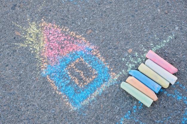 Disegnare casa con il gesso sull'asfalto disegno per bambini sulla strada, pastelli a gessetto colorati