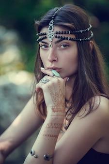 Disegnare mehndi per mezzo dell'henné su mani e un dorso della ragazza