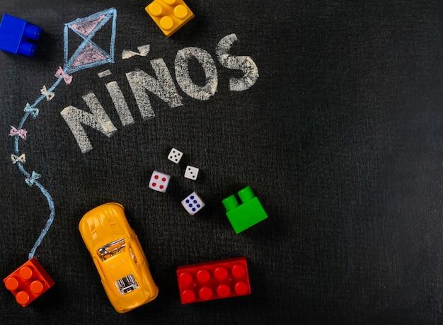 Disegno su carta vetrata. niños (spagnolo) scritto su lavagna e pezzi di assemblaggio. copia spazio