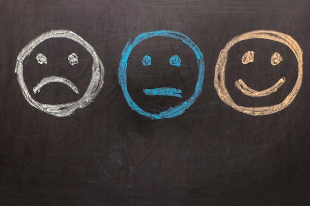 Disegnare emoticon infelici e felici su sfondo di lavagna