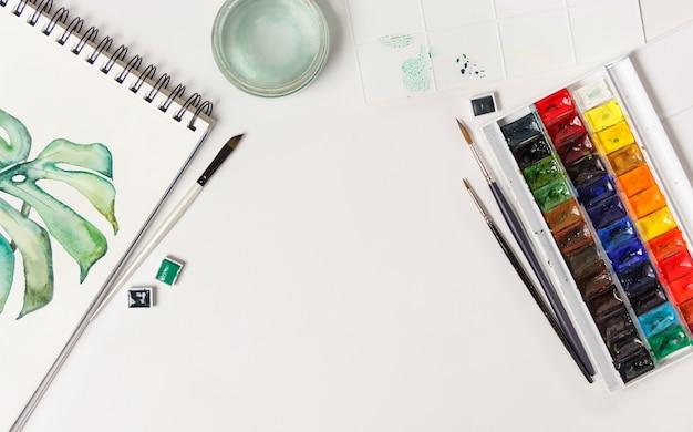 Disegni, pennelli, tavolozza e colori ad acquerello vista dall'alto. luogo di lavoro dell'artista