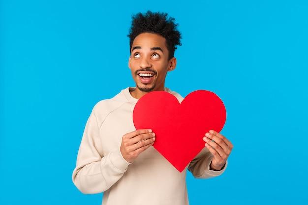 Drea, y e appassionato, allegro ragazzo afroamericano pensando a come rendere perfetto il giorno di san valentino