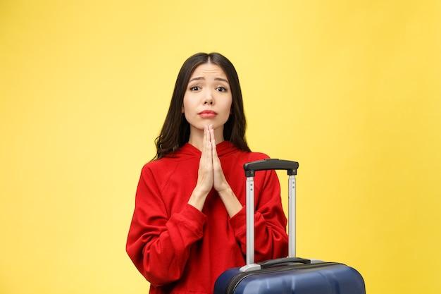 Sogna viaggi e vacanze. ritratto dello studio della donna abbastanza giovane eccitata con le mani in preghiera.