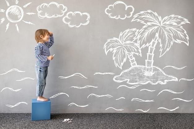 Sogna in grande bambino felice che gioca all'aperto un bambino divertente disegna un mare di gesso sul muro
