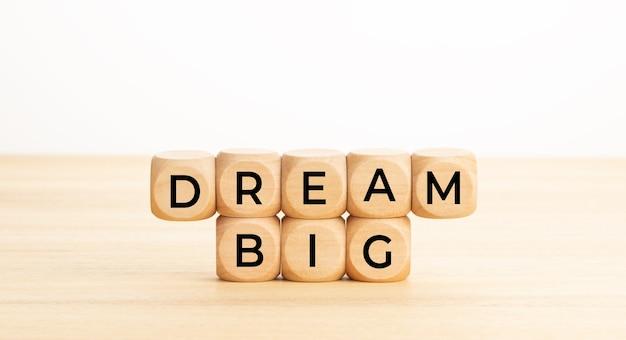 Sogna grandi parole su blocchi di legno sul tavolo
