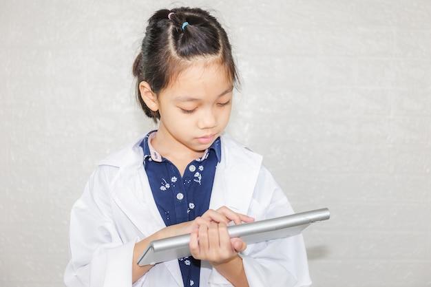 Concetto di carriera di sogno, medico della ragazza del ragazzino che digita alla tastiera del computer senza fili, ritratto di bambino felice in cappotto del medico con sfondo sfocato