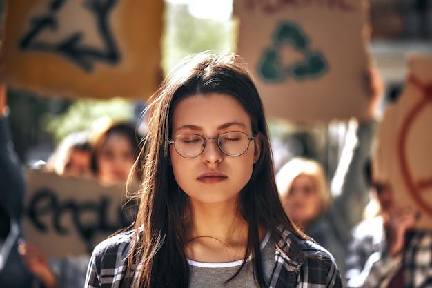 Sognare terra pulita giovane donna con gli occhiali che tiene gli occhi chiusi mentre sta all'aperto in