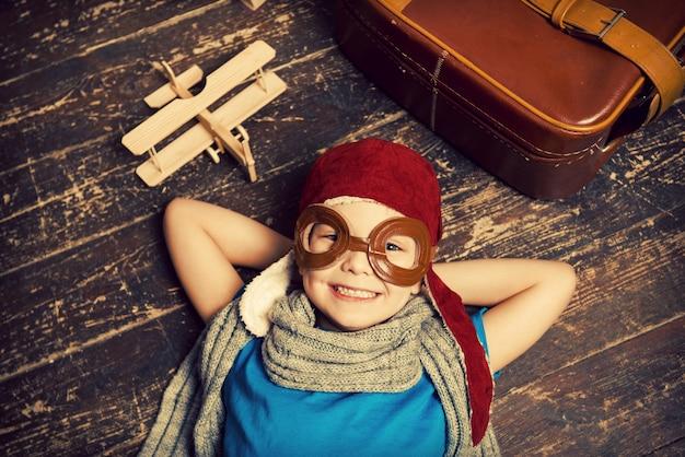 Sognando un grande cielo. vista dall'alto del ragazzino felice in copricapo pilota e occhiali da vista sdraiato sul pavimento di legno duro e sorridente mentre pialla in legno e valigetta posa vicino a lui