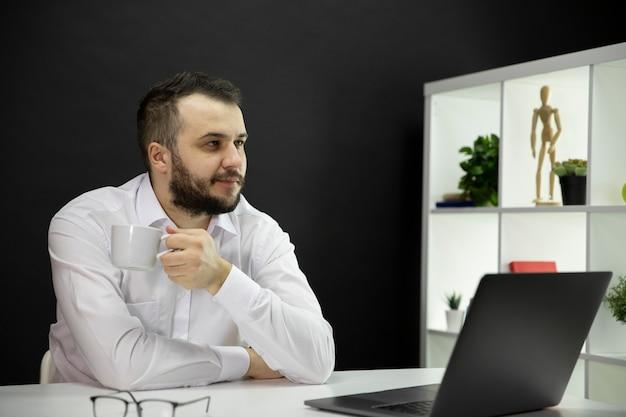 Sognando uomo bello con la tazza di caffè che si siede al tavolo davanti al computer portatile