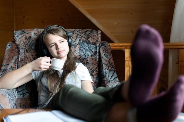 Sognare una ragazza adolescente si siede con una tazza in mano durante la pausa nel webinar online della scuola