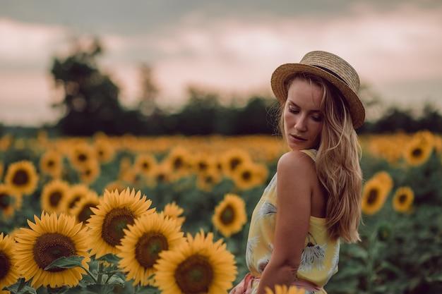 Sognando la giovane donna in abito giallo e cappello che tiene i capelli con le mani in un campo di girasoli in estate, vista dalla sua parte anteriore. guardando in basso. copia spazio