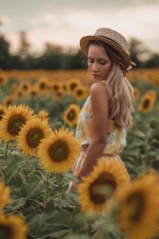 Sognando la giovane donna in abito giallo che tiene i capelli e il cappello con le mani in un campo di girasoli in estate, vista dal suo lato. guardando in basso. copia spazio