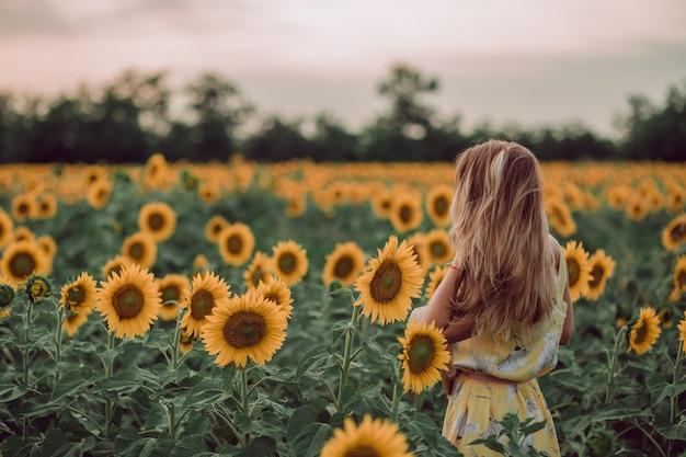 Sognando la giovane donna in abito giallo che tiene i capelli con le mani in un campo di girasoli in estate, vista dalla schiena. guardando di lato. copia spazio