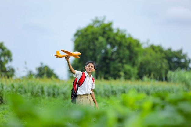 Sogni di volo! bambino indiano che gioca con aeroplano giocattolo al campo verde