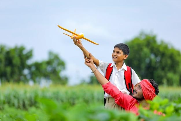 Sogni di volo! bambino indiano che gioca con l'aeroplano giocattolo con suo padre sul ciclo