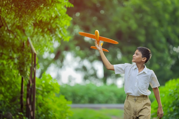 Sogni di volo! bambino indiano che gioca con aeroplano giocattolo