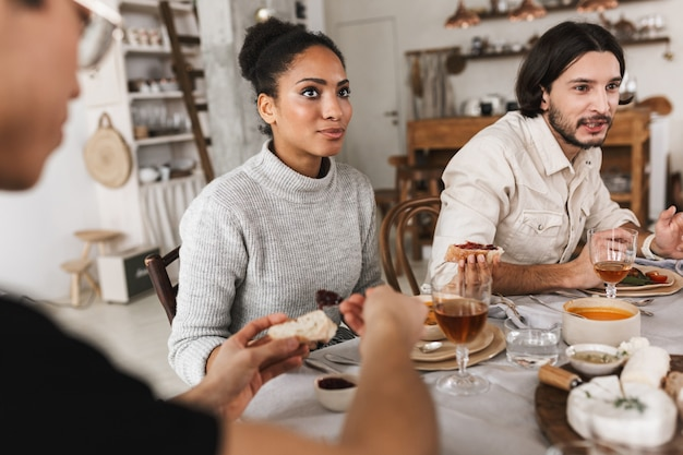 Donna afroamericana vaga con capelli ricci scuri che si siede al tavolo pensieroso