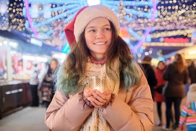 Bella ragazza teenager vaga in cappello della santa con la candela accesa