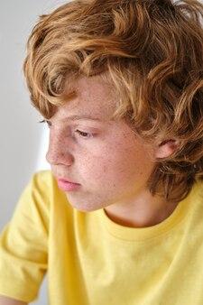 Ragazzo sognante con lentiggini sul viso e capelli castani