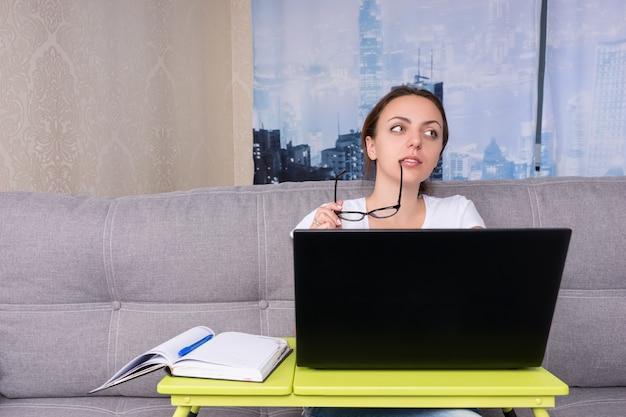 Donna d'affari sognante che sogna e si mette gli occhiali alla bocca mentre lavora su un laptop facendo i suoi affari da casa seduta su un divano nel soggiorno in un'atmosfera rilassata