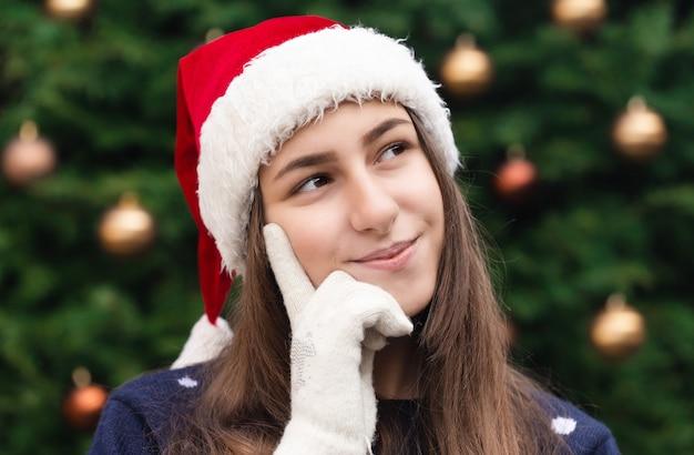 Donna sognante di natale. close up ritratto di donna che indossa un cappello di babbo natale con emozione. sullo sfondo di un albero di natale