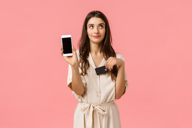 Sognante e civettuola bella giovane donna in abito, sognando in attesa di ordine di consegna online, in possesso di smartphone e carta di credito, mostrando lo schermo mobile