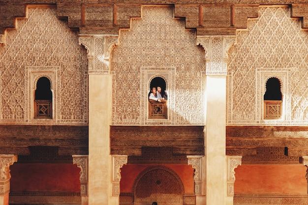 La coppia vaga vestita nel bianco chiude le passeggiate intorno alla città africana marrakesh in una sera soleggiata
