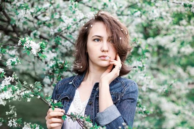 Sognante ragazza carina di aspetto europeo su uno sfondo di alberi in fiore.