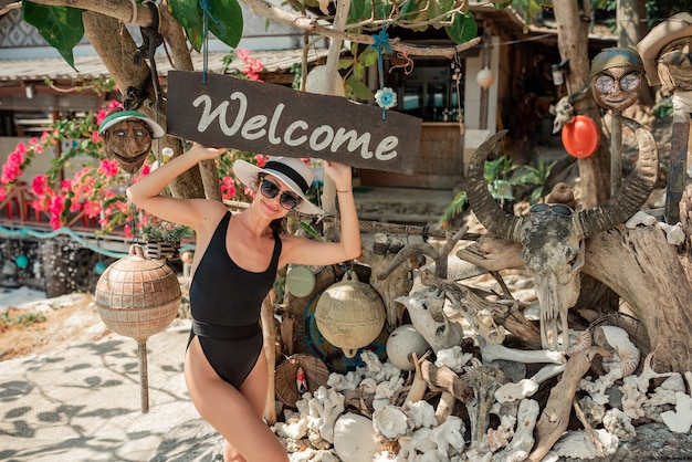 Donna vaga in costume da bagno nero sexy tsitting su una grande pietra in spiaggia tropicale e cappello di vimini. viaggio di vacanza estiva. concetto di stile di vita