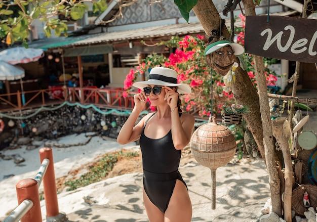 Donna vaga in costume da bagno nero sexy tsitting su una grande pietra in spiaggia tropicale e cappello di vimini.