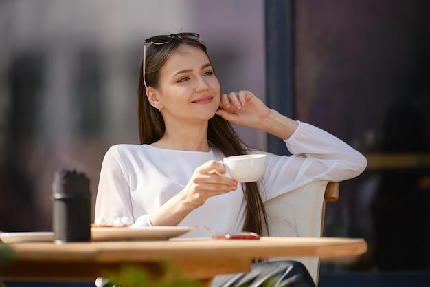 Giovane donna vaga che si siede sulla terrazza del caffè e beve cappuccino