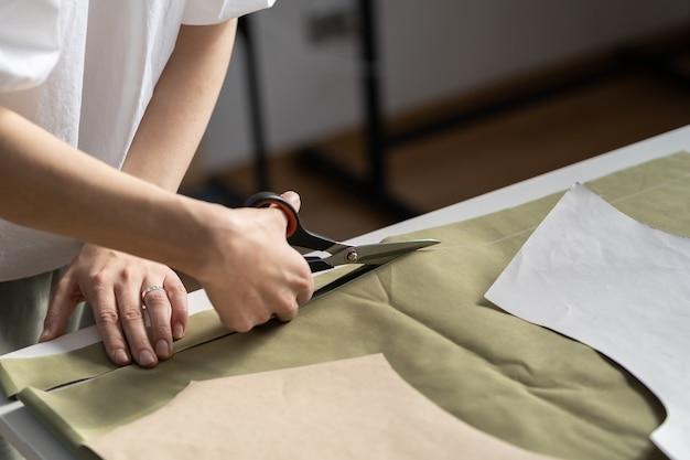 Modello tagliato da sarta nel laboratorio di sartoria primo piano della mano della donna designer usa le forbici per tagliare il tessuto