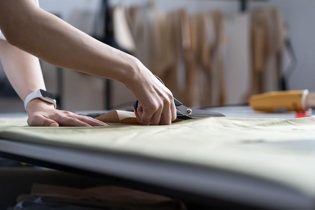 La mano del sarto usa le forbici tagliano il materiale del tessuto per cucire il primo piano del processo di lavoro nell'officina sartoria