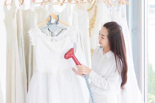 La sarta e la proprietaria della sua stanza stanno stirando un abito da sposa o un abito da sposa con un ferro da stiro a vapore.
