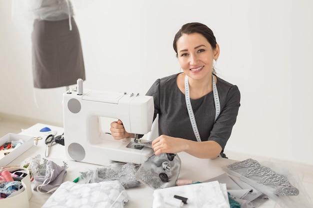 Sartoria, sarto e concept creativo - ritratto di stilista con macchina da cucire su superficie bianca