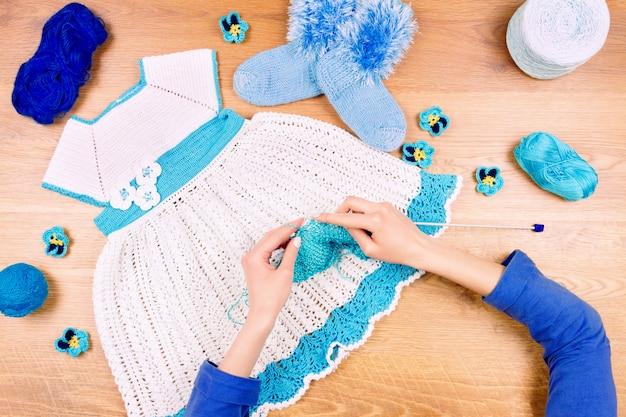 Luogo di lavoro sarta. maglieria femminile della donna che fa vestito blu per le neonate