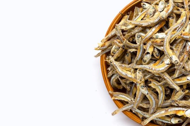 Acciughe essiccate in cesto di bambù su sfondo bianco