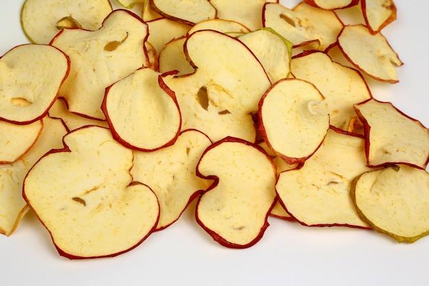 Primo piano secco delle fette di mela su fondo bianco