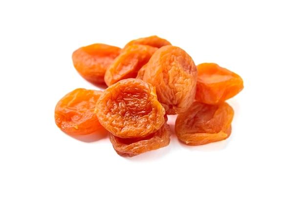 Albicocche secche isolati su sfondo bianco. mucchio di frutta secca albicocca, fuoco selettivo