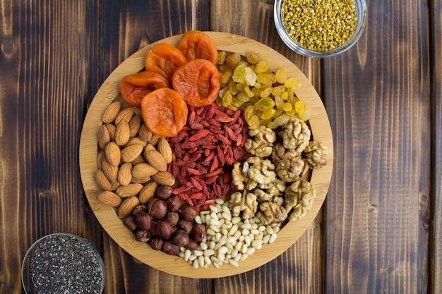 Albicocche secche, uvetta, bacche di goji, noci diverse, semi di chia e polline d'api sul tagliere rotondo sullo sfondo di legno marrone. vista dall'alto.