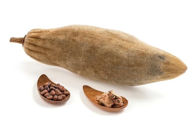 Frutta secca e seme del baobab isolati sulla superficie bianca.