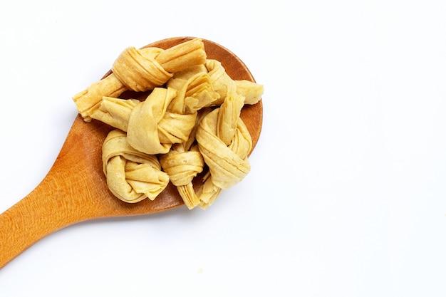 Nodo di cagliata di fagioli secchi sul cucchiaio woon su bianco. copia spazio