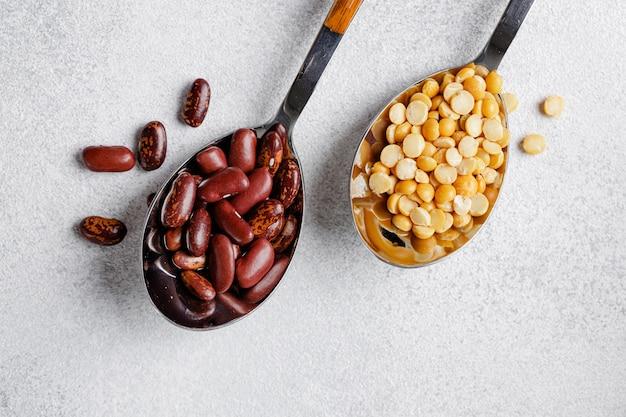 Fagioli secchi in cucchiai di legno sul tavolo